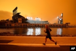 FILE - Under darkened skies from wildfire smoke, a jogger makes his way along McCovey Cove outside Oracle Park, Sept. 9, 2020, in San Francisco.