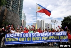 FILE - Filipino activists march to protest against the presence of Chinese vessels in disputed parts of the South China Sea, at the Chinese Embassy in Makati City, Philippines, April 9, 2019.