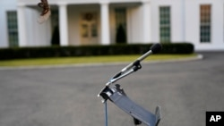 An unused microphone stand sits outside the West Wing at the White House, Tuesday, Jan. 19, 2021, in Washington. On President Donald Trump's last full day in office, there was an eerie quiet, with no public events scheduled, his last event being Jan…