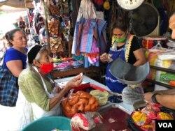 La comerciante Rina Castillo despacha alimentos básicos a los clientes que abarrotaron su mercado.