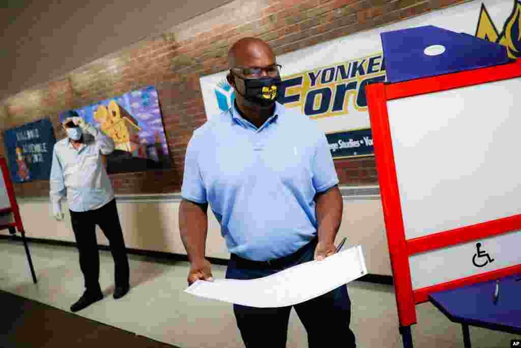 یک رای دهنده در انتخابات مقدماتی نیویورک. جمال بومن یک آمریکایی آفریقایی تبار، الیوت اِنگل ۷۳ ساله، رئیس دموکرات کمیته امور خارجی مجلس نمایندگان آمریکا را به چالش گرفته است. آقای اِنگل ۱۶ دوره نماینده بوده است.
