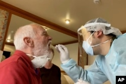 FILE - In this image from a video, Paul Molesky, left, gets a DNA swab test in his cabin room on the Diamond Princess, anchored at a port in Yokohama, near Tokyo, Feb. 13, 2020.