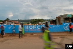 People walk across a bridge with a message written on the barriers advocating personal efforts to stem the spread of the COVID-19 coronavirus in the Kibera slum, Nairobi, on April 14, 2020.