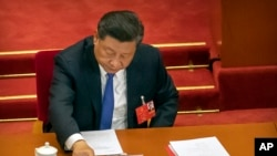 Chinese President Xi Jinping reaches to vote on a piece of national security legislation concerning Hong Kong during the closing session of China's National People's Congress (NPC) in Beijing, Thursday, May 28, 2020. China's ceremonial legislature…