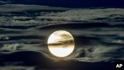 FILE - The full moon shines surrounded by clouds in the outskirts of Frankfurt, Germany, Sept. 2, 2020.