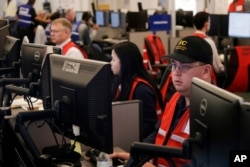 FILE - Pacific Gas and Electric employees work in the PG&E Emergency Operations Center in San Francisco, Oct. 10, 2019.