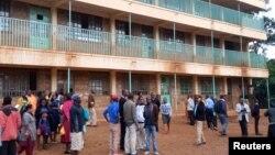 Para orang tua dan guru berkumpul di dekat lokasi terjadinya insiden di SD Kakamega, Kenya, Senin (3/2).