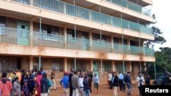 Parents and teachers gather near the scene of a stampede at the Kakamega primary school in Kakamega, Kenya, Feb. 3, 2020.