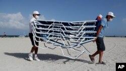Radnici nose ležaljke sa plaže u Miami Beachu, na Floridi, dok se približava uragan Isaias.