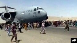 美國空軍C-7運輸機在喀布爾國際機場起飛時上百人在跑道上跟隨奔跑。 (2021年8月16日)