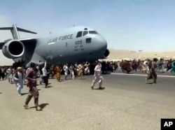 Hundreds of people run alongside a U.S. Air Force C-17 transport plane as it moves down a runway of the international airport, in Kabul, Afghanistan, Aug.16. 2021.