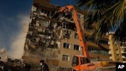 Un trabajador pasa frente a un edificio dañado por el sismo del 30 de octubre que obreros están demoliendo. Esmirna, Turquía, 4 de noviembre de 2020.