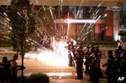 A firework explodes by a police line as demonstrators gather to protest the death of George Floyd, May 30, 2020, near the White House in Washington, D.C.