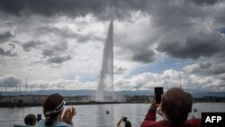 People applaud during a ceremony marking the restarting of Geneva's landmark fountain, known as Jet d'Eau, following the COVID-19 outbreak, June 11, 2020.