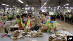In this Oct. 24, 2017, photo, garment workers sew clothes at Pro Sports factory in Nam Dinh province, Vietnam. U.S. President Donald Trump's decision to withdraw from a far-reaching Pacific Rim trade pact is having scant impact on fast-growing trade…