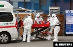 A confirmed coronavirus patient is wheeled to a hospital at Chuncheon, South Korea, Feb. 22, 2020.