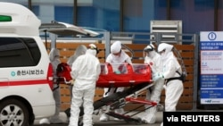A confirmed coronavirus patient is wheeled to a hospital at Chuncheon, South Korea, February 22, 2020. Yonhap via REUTERS ATTENTION EDITORS - THIS IMAGE HAS BEEN SUPPLIED BY A THIRD PARTY. SOUTH KOREA OUT. NO RESALES. NO ARCHIVE.