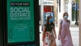 FILE - Two women walk past a social distance sign at City Creek Center in Salt Lake City, Utah, May 6, 2020.