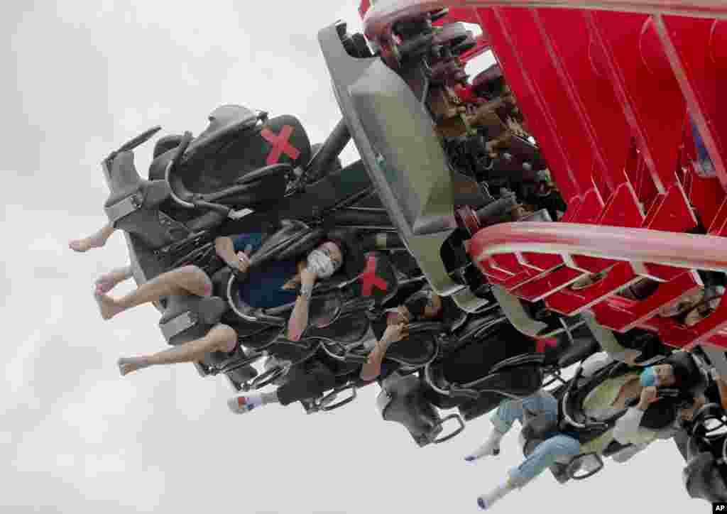 تصویری از گروهی از گردشگران در یک پارک بازی در تایلند. بعد از مدتها از شیوع کرونا این پارک باز شده و همانطوری که در عکس مشخص است، مردم با ماسک در صندلی ها با فاصله نشستهاند.
