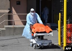 A medical staffer moves the body of a coronavirus victim from the Wyckoff Heights Medical Center to a refrigerated truck in Brooklyn, New York, April 2, 2020.