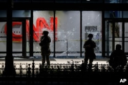 Members of the Georgia National Guard stand in front of shattered glass at the CNN Center in the aftermath of a demonstration against police violence, May 30, 2020, in Atlanta.