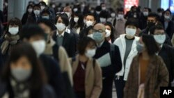 A station passageway is crowded with face mask wearing commuters during a rush hour Monday, April 20, 2020, in Tokyo. Japan's Prime Minister Shinzo Abe expanded a state of emergency to all of Japan from just Tokyo and other urban areas as the virus…