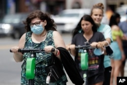 A woman wears a mask as she rides a scooter, June 30, 2020, in Nashville, Tenn.