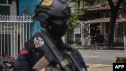 ເຈົ້າໜ້າທີ່ອິນໂດເນເຊຍຢືນຍາມຢູ່ບ່ອນເກີດເຫດລະເບີດແຕກຢູ່ນອກໂບດແຫ່ງນຶ່ງໃນເມືອງ Makassar ໃນວັນທີ 28 ມີນາ, 2021. (ພາບໂດຍ INDRA ABRIYANTO / AFP)