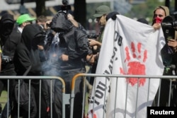 FILE - Antifa counterprotesters, rallying against right-wing group Patriot Prayer, light a smoke grenade in Portland, Oregon, Sept. 10, 2017.