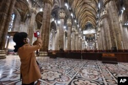 A tourist wearing a face mask takes pictures inside the Duomo gothic cathedral as it reopened to the public after being closed due to the COVID-19 virus outbreak in northern Italy, in Milan, March 2, 2020.