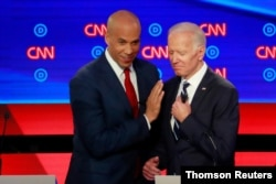 U.S. Senator Cory Booker and former Vice President Joe Biden talk during a commercial break on the second night of the second U.S. 2020 presidential Democratic candidates debate in Detroit, July 31, 2019.