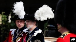 FILE - Britain's Prince William, left, and Spain's King Felipe sit in a carriage after the Order of The Garter Service at Windsor Castle in Windsor, June 17, 2019.