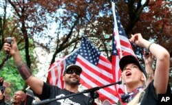 Patriot Prayer adlı grubun lideri (solda) Joey Gibson