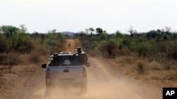 FILE - Anti-rhino poaching troops simulate a hunt for poachers in the Madikwe Game Reserve, Botswana, Nov. 8, 2013.