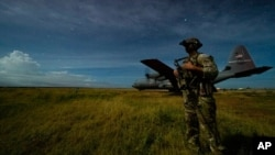 Një ushtarak i Batalionit 186 të Këmbësorisë duke ruajtur perimetrin për një aeroplan transporti të Skuadriljes 75, në një vendndodhje të panjoftuar në Somali (28 qershor 2020)