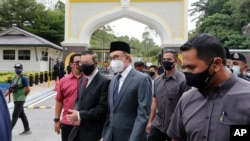Malaysia opposition leaders Anwar Ibrahim, center, and Lim Guan Eng, left, leave National Palace after meeting the King in Kuala Lumpur, Aug. 17, 2021.