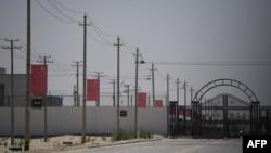 新疆和田一處據信為關押著維吾爾穆斯林少數民族的集中營設施外沿路高掛中國國旗。 (2019年5月31日)