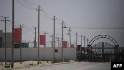 新疆和田一處據信為關押著維吾爾穆斯林少數民族的集中營設施外沿路高掛中國國旗。(2019年5月31日)