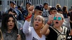 Para pengunjuk rasa meneriakkan slogan-slogan selama protes yang sedang berlangsung ketika polisi anti huru hara berdiri di depan gedung Kementerian Keuangan di Beirut, Lebanon, 29 November 2019. (Foto: AP)