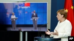 German Chancellor Angela Merkel, right, speaks as she holds a video news conference with European Council President Charles Michel, right on screen, and European Commission President Ursula von der Leyen, in Berlin, Sept. 14, 2020.