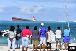 Bystanders look at the MV Wakashio bulk carrier that had run aground and from which oil was leaking, near Blue Bay Marine Park in southeast Mauritius, Aug. 6, 2020.