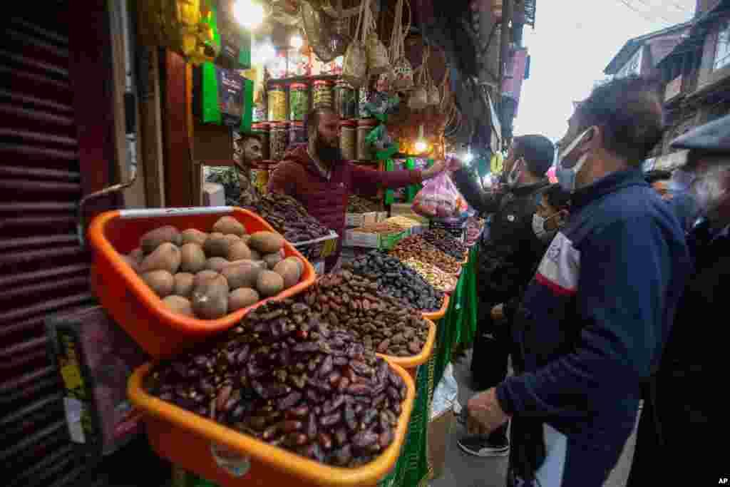 مردم مشغول خرید از یک فروشگاه خشکبار، قبل از زمان افطار در اولین روز ماه رمضان در سرینگر، کشمیر