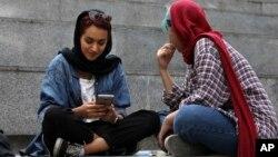 تہران میں ایک خاتون اپنا موبائل فون چیک کر رہی ہے کہ آیا سگنلز ہیں یا نہیں۔