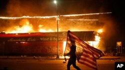 A protester carries a U.S. flag upside down, a sign of distress, next to a burning building, May 28, 2020, in Minneapolis.