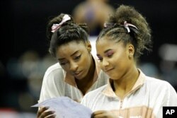 FILE - Simone Biles, left, and Jordan Chiles look over a rotation schedule during practice for the senior women's competition at the 2019 U.S. Gymnastics Championships, in Kansas City, Mo., Aug. 11, 2019.