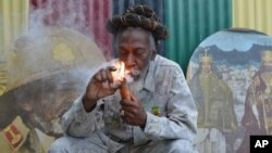 """FILE - In this Aug. 28, 2014 file photo, legalization advocate and reggae legend Bunny Wailer smokes a pipe stuffed with marijuana during a """"reasoning"""" session in a yard in Kingston, Jamaica."""