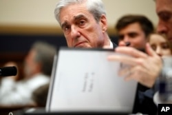 Former special counsel Robert Mueller, checks pages in the report as he testifies before the House Judiciary Committee hearing on his report on Russian election interference, on Capitol Hill, July 24, 2019 in Washington.