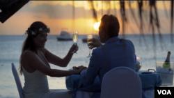 한 신혼부부가 해변에서 신혼여행을 즐기고 있다.