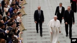Pope Francis walks in the Paul VI Hall at the end of his weekly general audience at the Vatican, Aug. 21, 2019.