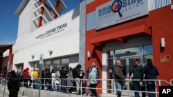 People wait in line for help with unemployment benefits at the One-Stop Career Center in Las Vegas, March 17, 2020.
